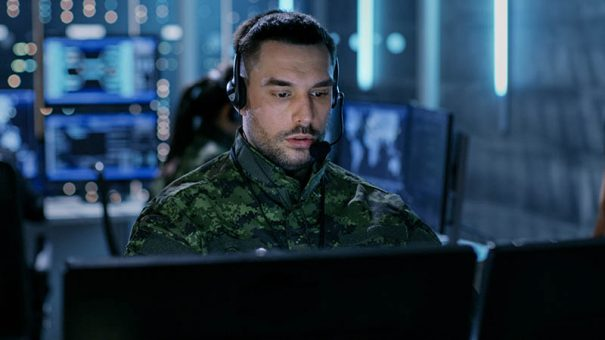 Close-up shot of Military Technical Support Professional Gives Instructions Using Headset. He's in a Monitoring Room with Other Officers and Many Working Displays in Background.